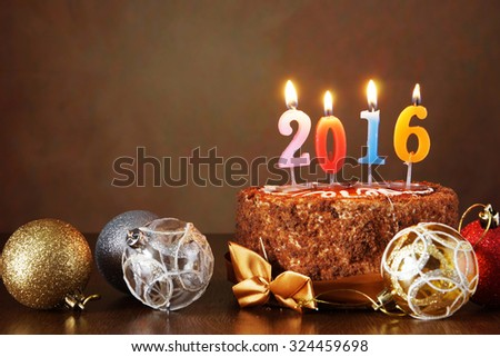 New Year 2016 still life. Chocolate cake and decorative tree balls with burning candles on brown background - stock photo