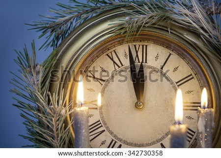 New Year time concept. Clock with candles and christmas tree branch - stock photo