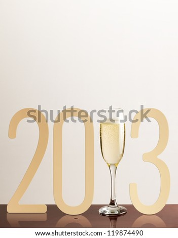 New year typo for 2013 with glass of sparkling champagne. - stock photo