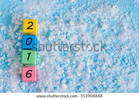 New 2016 Year wood number on color wooden cubes with snow and empty space for text. Happy new year concept postcard. - stock photo