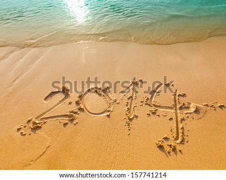 New Year 2014 written in sand on the beach - stock photo