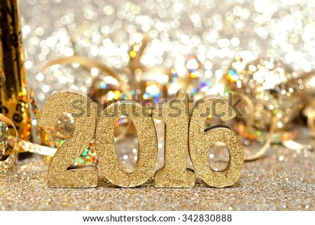 New Years Eve 2016 golden numbers and decorations with twinkling gold background - stock photo