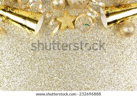 New Years Eve top border of streamers and decorations over a glittery gold background                  - stock photo