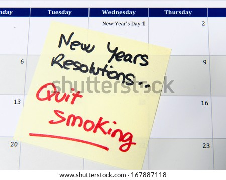 New Years Resolution quit smoking post it note on calendar - stock photo