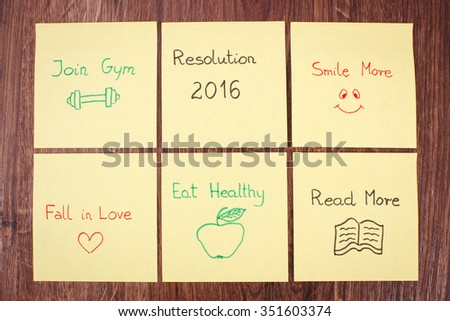 New years resolution written on yellow sheet of paper lying on wooden background - stock photo