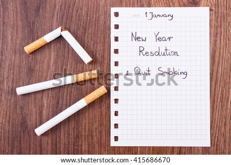 New years resolutions quit smoking written on sheet of paper and broken cigarette, concept of healthy lifestyle, world no tobacco day - stock photo