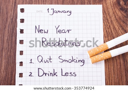New years resolutions quit smoking written on sheet of paper and cigarette, concept of healthy lifestyle, world no tobacco day - stock photo
