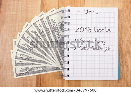 New years resolutions save money and get better job written in notebook and currencies dollar  - stock photo