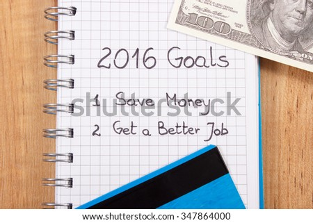 New years resolutions save money and get better job written in notebook and currencies dollar with credit card - stock photo