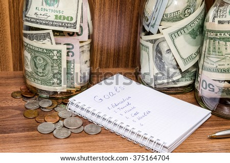New years resolutions with dollar in glass jar, coins on wooden table