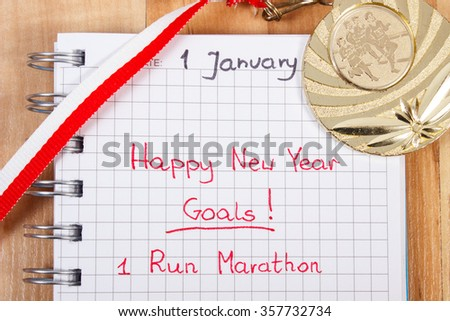 New years resolutions written in notebook and gold medal, concept of sports achievement and healthy lifestyle