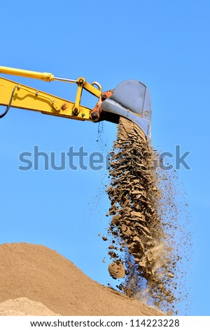new yellow excavator working on sand dunes. Scoop close-up - stock photo