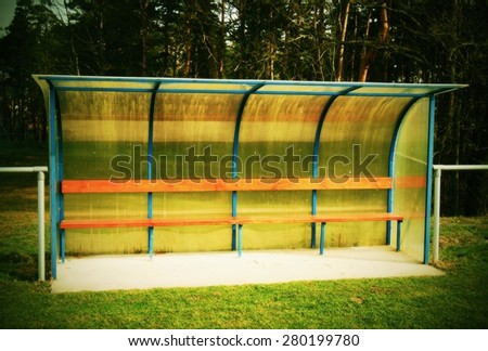 New yellow plastic roof above wooden seats on outdoor stadium players bench. - stock photo