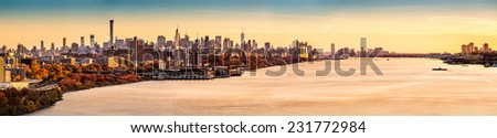 New York and Hudson River panorama as viewed from George Washington Bridge at sunset. Manhattan buildings reflect an orange glow from the last rays of the day. - stock photo