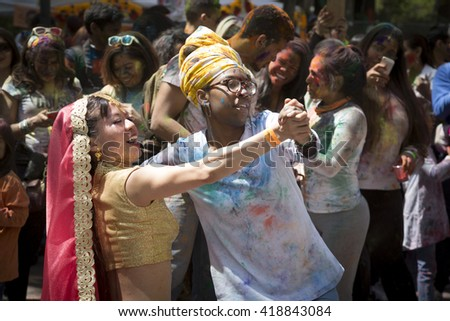 NEW YORK - APR 30 2016: A female member of NYC Bhangra and a spectator dance together in the crowd at the Holi Hai Festival of Colors in Dag Hammerskjold Plaza in New York April 30, 2016.