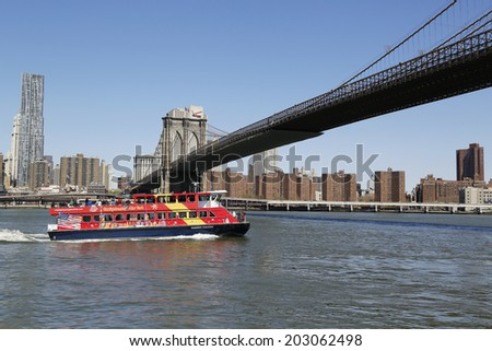 NEW YORK - APRIL 24:City Sightseeing boat under Brooklyn Bridge on April 24, 2014 Gray Line Worldwide operates local sightseeing tours across the world.In 2004 its carriers handled 25 million tourists - stock photo