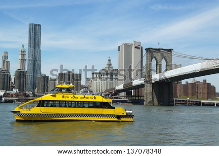 NEW YORK - APRIL 30: New York City Water Taxi with NYC skyline and Brooklyn Bridge seen from Brooklyn Bridge Park  on April 30, 2013. NYC Water Taxi has been servicing NYC commuters since 2002 - stock photo