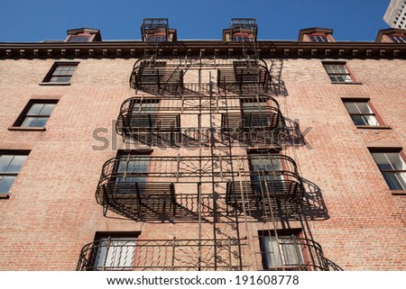 NEW YORK - APRIL 6: Ornate fire escapes on the side of a brick building in Lower Manhattan, New York City. Photo taken April 6, 2014.