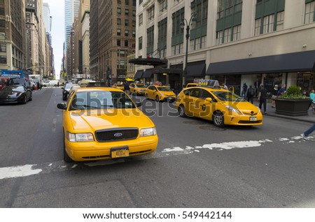 NEW YORK - APRIL 28, 2016: Typically yellow medallion taxicabs in front of Macy's department store. They are widely recognized icons of the city and come in two varieties: yellow and green.