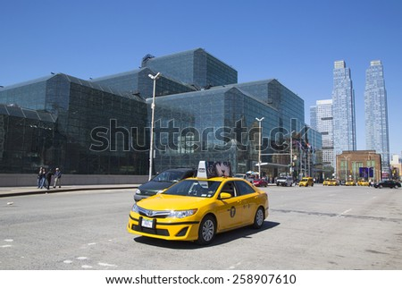 NEW YORK - APRIL 24, 2014: Yellow taxi in front of Javits Convention Center in Manhattan. The convention center has a total area space of 1,800, 000 square ft and has 840,000 square ft of total space  - stock photo