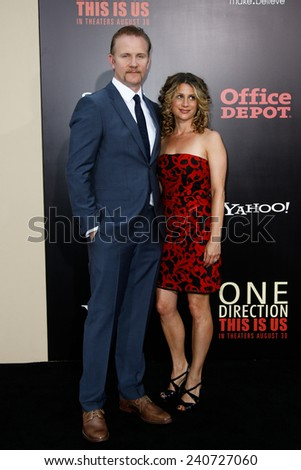 NEW YORK-AUG 26: Director Morgan Spurlock (L) and guest attend the New York premiere of 'One Direction: This Is Us' at the Ziegfeld Theater on August 26, 2013 in New York City. - stock photo