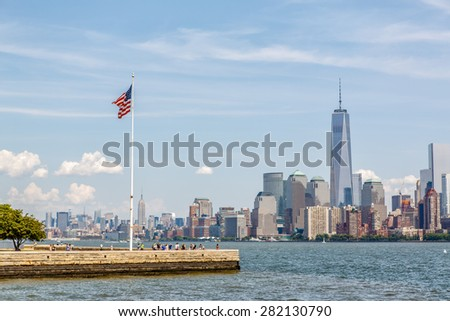 NEW YORK - AUGUST 11: American flag on Liberty Island in New York Harbor and Manhattan skyline on August 11, 2014. Manhattan is one of the worlds leading cultural and economic centers. - stock photo