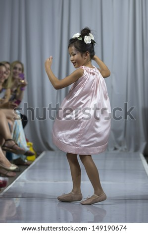 NEW YORK - AUGUST 5: Girl walks runway for debut L'Offciel Enfant fashion show at Highline Loft on August 5, 2013 in New York City - stock photo