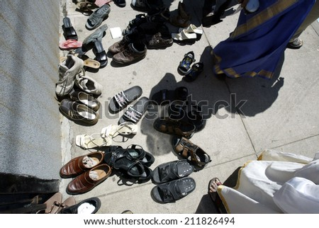 NEW YORK - AUGUST 30: Hindus leave their shoes outside the Sri Ganesa Chaturthi prior to praying in celebration of the birth of Ganesh on August 30, 2003 in Flushing, New York. - stock photo