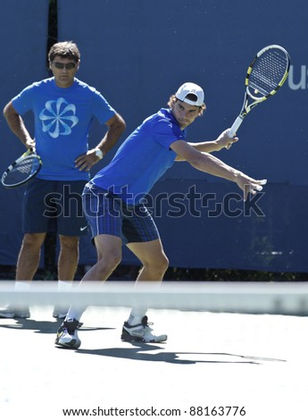 NEW YORK - AUGUST 29: Rafael Nadal of Spain practices with coach Tony Nadal watches at USTA Billie Jean King National Tennis Center during US Open on August 29, 2011 in New York City. - stock photo