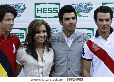 NEW YORK - AUGUST 28: The Jonas Brothers (L-R) Nick, Joe and Kevin and singer Demi Lovato arrive at the Arthur Ashe Kids Day at US Open August 28, 2010 in New York City - stock photo