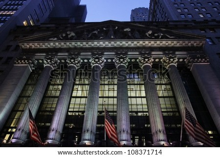 NEW YORK - CIRCA 2012: American flags flow in the wind at the New York Stock Exchange on Wall Street,  circa 2012 in New York City. - stock photo