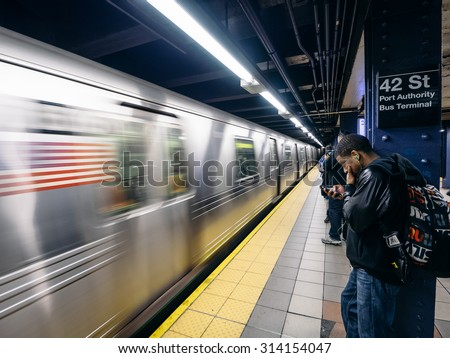 NEW YORK - CIRCA OCT, 2014:People wait at a subway station in New York. With 1.67 billion annual rides, New York City Subway is the 7th busiest metro system in the world.