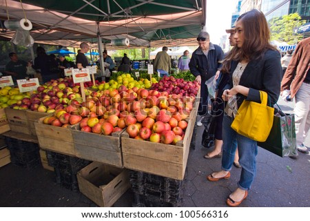 NEW YORK CITY - APR. 20: Woman selects produce at Union Square Greenmarket in NYC on Apr 20, 2012. This world famous farmers' market began in 1976 and has grown to 140 farmers during peak season.