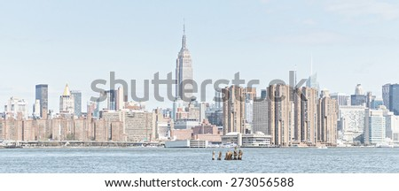 NEW YORK CITY - APRIL 21: New York City Manhattan skyline with Empire State Building over East River with vintage effect on April 21, 2015 in New York City.  - stock photo