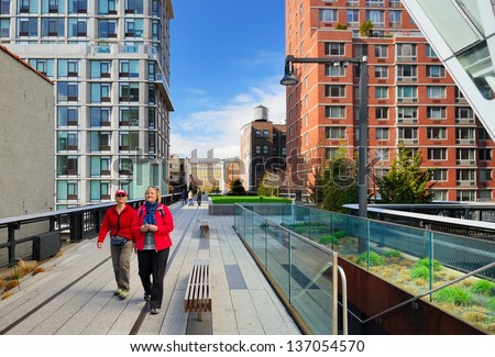 NEW YORK CITY - APRIL 13: Pedestrians stroll atop the High Line April 13, 2013 in New York, NY. The former elevated railroad was abandoned in 1980 but redeveloped as a greenway opening in 2009. - stock photo