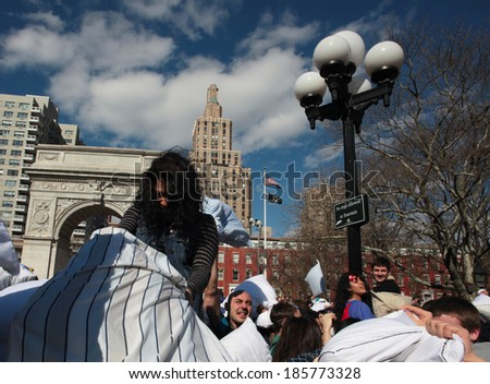 NEW YORK CITY - APRIL 5 2014: the first Saturday of April is International Pillow Fight Day, observed this time at Washington Square Park in Lower Manhattan. Young woman gaining height advantage - stock photo