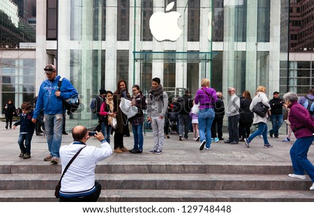 NEW YORK CITY-APRIL 1:Visitors take family photos at Apple's flagship store on April 1, 2012 on 5th Avenue in NYC .The store is one of the most photographed sites in NYC, reports Forbes Magazine. - stock photo