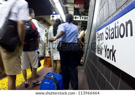 NEW YORK CITY - AUG 29:  Commuters bustle on the Long Island Railroad subway platform at Pennsylvania Station NYC on Aug. 29, 2012.  Penn Station is a train major hub serving 300,000 commuters a day. - stock photo
