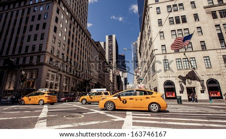NEW YORK CITY - AUGUST 13: Yellow taxis rides on 5th Avenue on August 13, 2013 in New York, USA. 5th Avenue is a central road of Manhattan, the most expensive shops and apartmens situated here