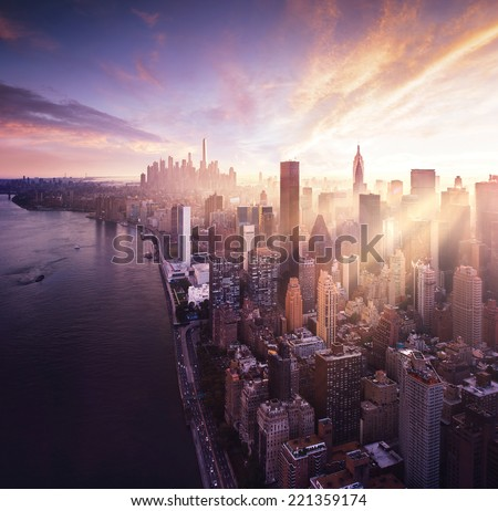 New York City - beautiful colorful sunset over manhattan fit sunbeams between buildings - stock photo