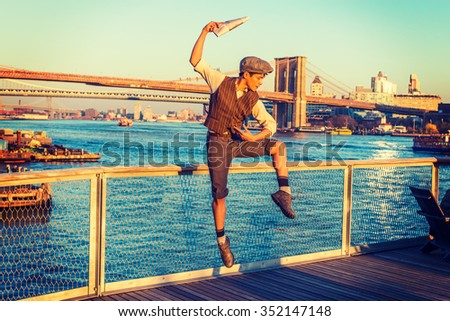 New York City Boy. Wearing newsboy cap, shirt, vest, pants, leather boot shoes, Asian American guy jumping into air at harbor in sunset, raising arm, holding newspaper, dancing with joy, excitement.  - stock photo