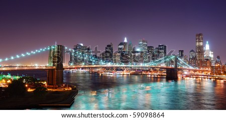 New York City Brooklyn Bridge and Manhattan skyline panorama view with skyscrapers over Hudson River illuminated with lights at dusk after sunset. - stock photo