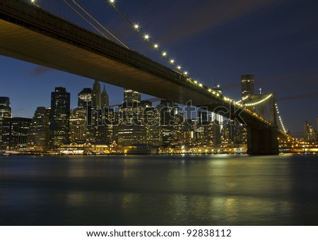 New York City, Brooklyn Bridge and Manhattan skyline with skyscrapers over Hudson River, at dusk after sunset.