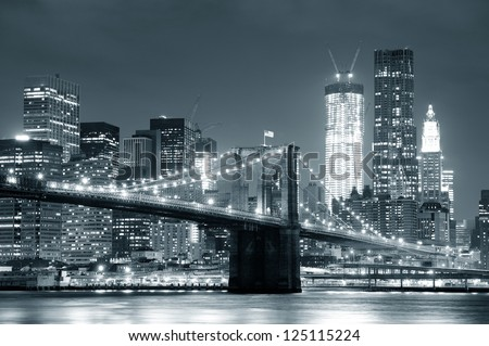 New York City Brooklyn Bridge black and white with downtown skyline over East River. - stock photo