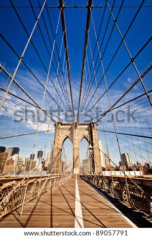 New York City Brooklyn Bridge in Manhattan closeup with skyscrapers and city skyline over Hudson River. - stock photo