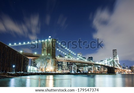New York City Brooklyn Bridge skyline with skyscrapers over Hudson River illuminated with lights at dusk.