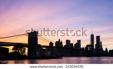 New York City Brooklyn Bridge with downtown skyline over East River during sunset - stock photo