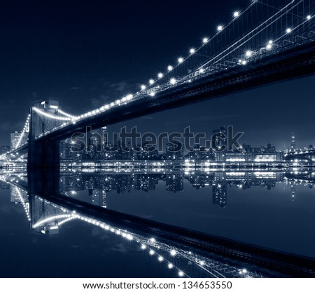 New York City, Brooklyn Bridge with reflections on water - stock photo