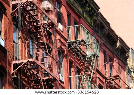 New York City Buildings at the street of chinatown with fire escapes. - stock photo