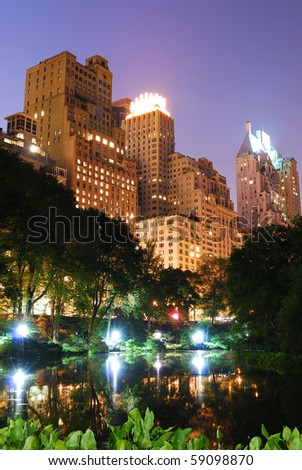 New York City Central Park at night with Manhattan skyscrapers lit with light. - stock photo